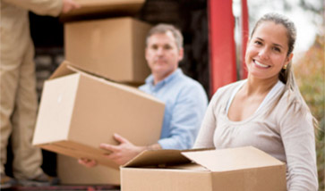 smiling couple loads boxes on truck